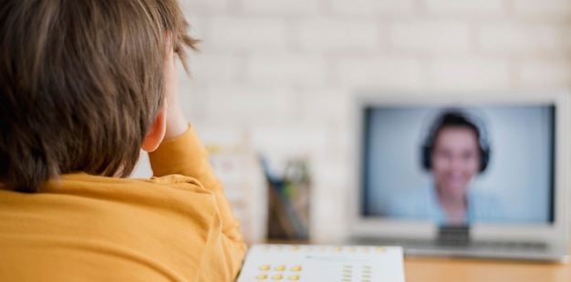 Вид сзади ребенка, обучаемого дома через онлайн-класс Бесплатные Фотографии
