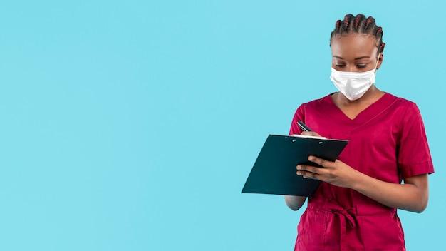女医がマスクとクリップボードに書き込み 無料写真