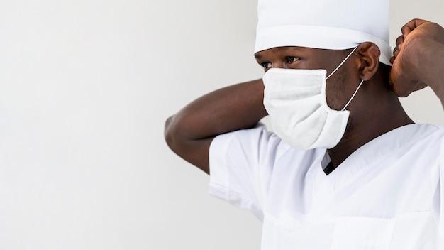 マスクの肖像画を置く専門の男性医師 無料写真