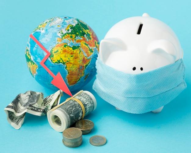 世界的な経済危機とマスクをした貯金箱 無料写真