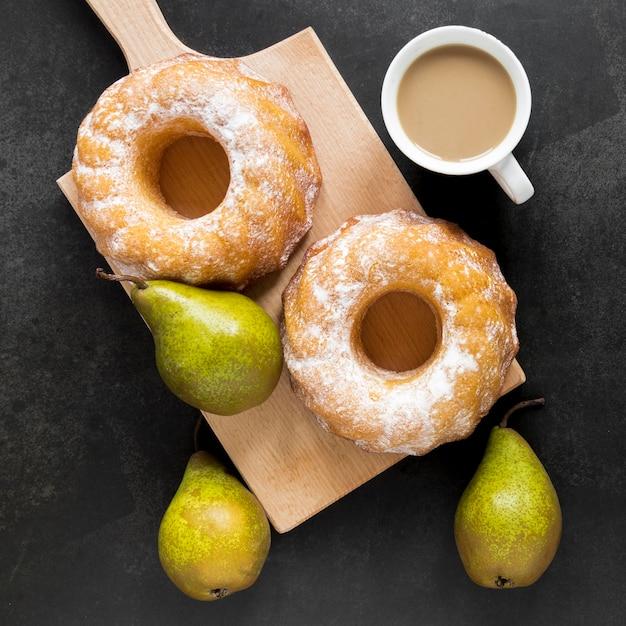 梨とコーヒーのまな板にドーナツのトップビュー 無料写真