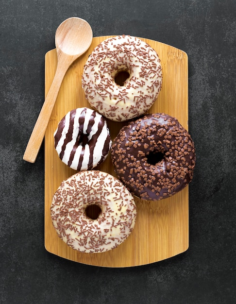 Вид сверху пончики на разделочную доску с ложкой Бесплатные Фотографии