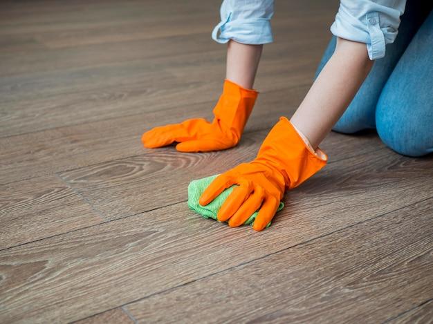 ゴム手袋で床を掃除するクローズアップ 無料写真