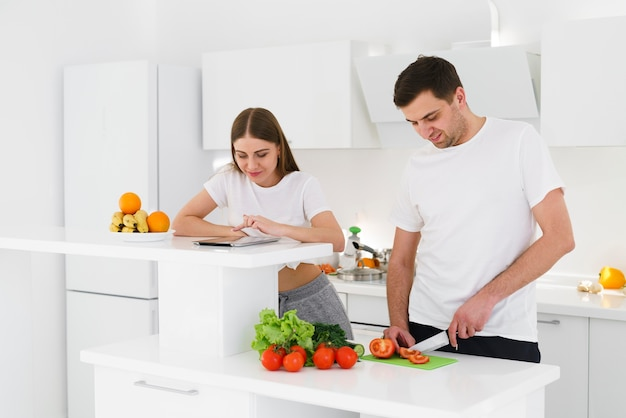 Высокий угол молодая пара готовит салат Бесплатные Фотографии