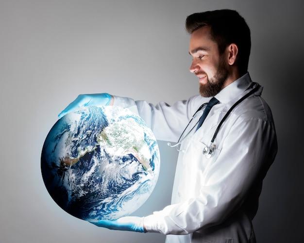 世界を表すグローブを保持しているハンサムな医者 無料写真