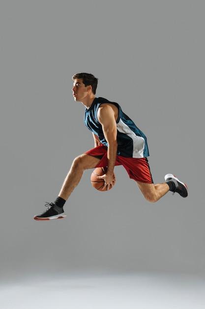 サイドビューの若い男がバスケットボールをしながらジャンプ 無料写真