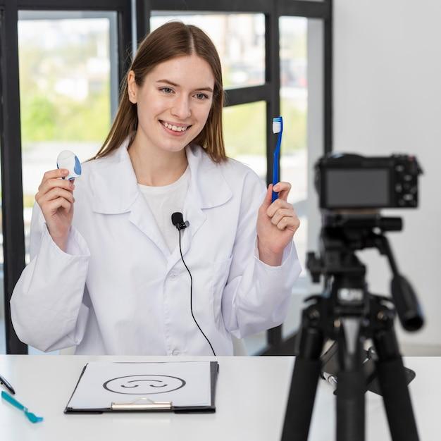 歯科付属品を提示するブロガーの肖像画 無料写真