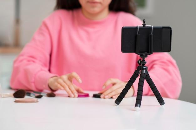 彼女のメイクアップセッションを記録するブロガー 無料写真