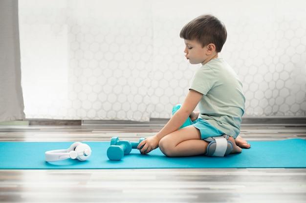 Прелестный ребенок сидит на коврик для йоги Бесплатные Фотографии