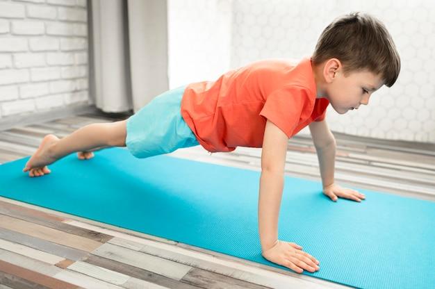Прелестный мальчик тренируя детенышей дома Бесплатные Фотографии