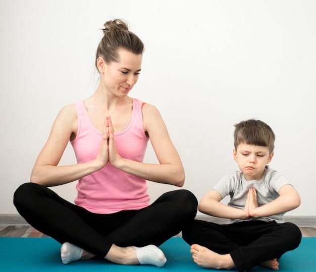 Йога прелестного молодого мальчика практикуя с матерью Бесплатные Фотографии