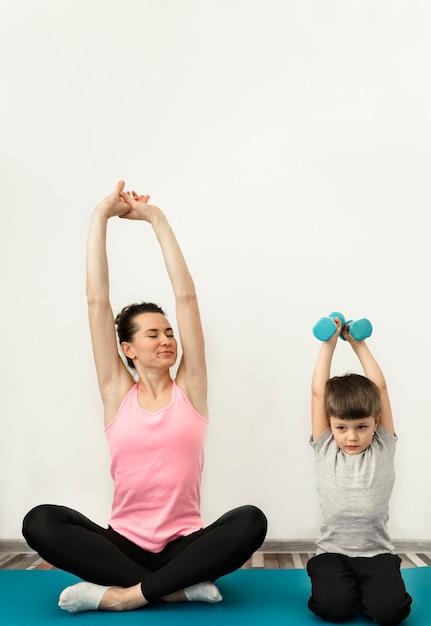 Прелестный мальчик тренируется вместе с матерью Бесплатные Фотографии