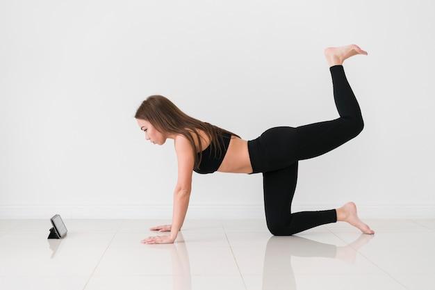 Женщина делает упражнения фитнес с мобильного телефона Бесплатные Фотографии