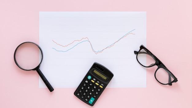 Экономическая диаграмма на листе бумаги с лупой Бесплатные Фотографии