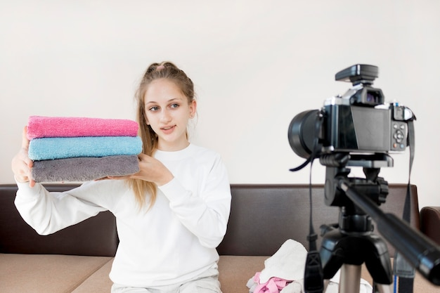 Средний снимок девушки складывает полотенца в домашних условиях Бесплатные Фотографии