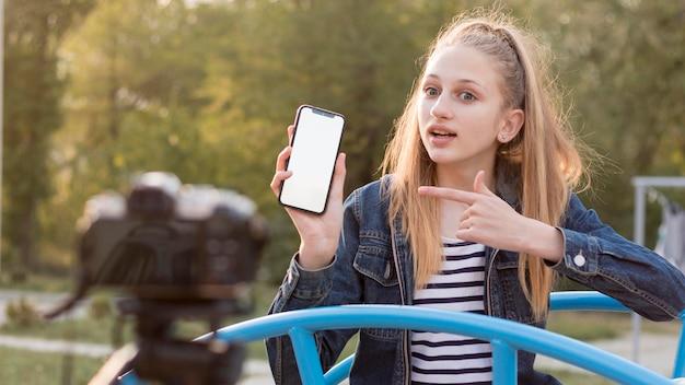 Средний снимок девушка держит смартфон Бесплатные Фотографии