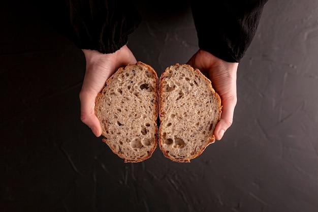 Руки крупного плана держа взгляд сверху хлеба Бесплатные Фотографии