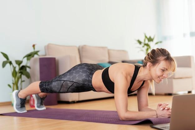 Женщина занимается спортом на дому Бесплатные Фотографии