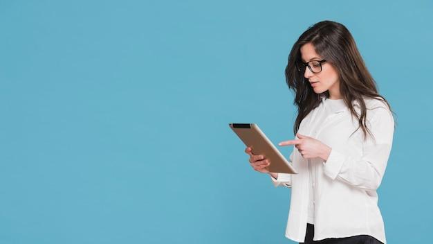 彼女のタブレットのコピースペースを指す女性 無料写真
