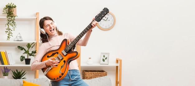 ギターとソファの上のコピースペース女性 無料写真