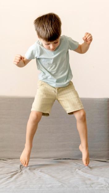 Полный выстрел мальчик прыгает на диване Бесплатные Фотографии