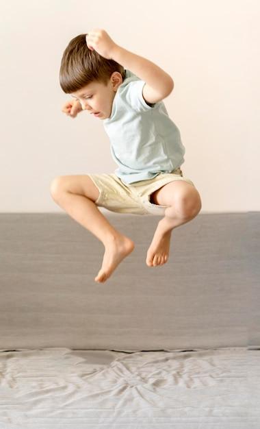 ソファの上でジャンプフルショットの子供 無料写真