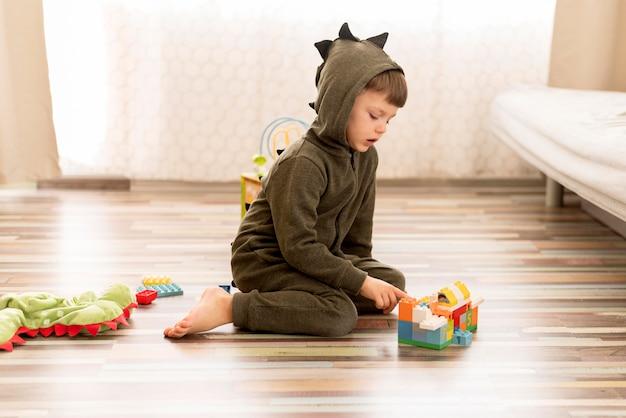ドラゴンコスチュームを着たフルショットの子供 無料写真