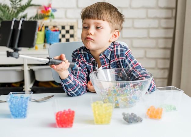 Мальчик с разноцветными шариками из гидрогеля Бесплатные Фотографии
