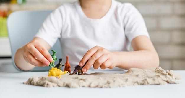Крупным планом ребенок играет с динозаврами Бесплатные Фотографии
