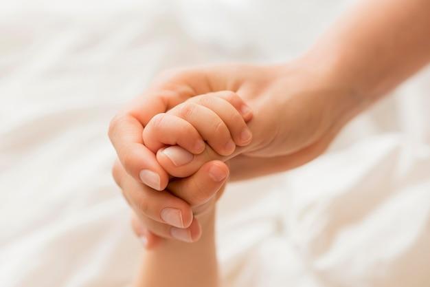 Крупным планом мама и ребенок, держась за руки Бесплатные Фотографии