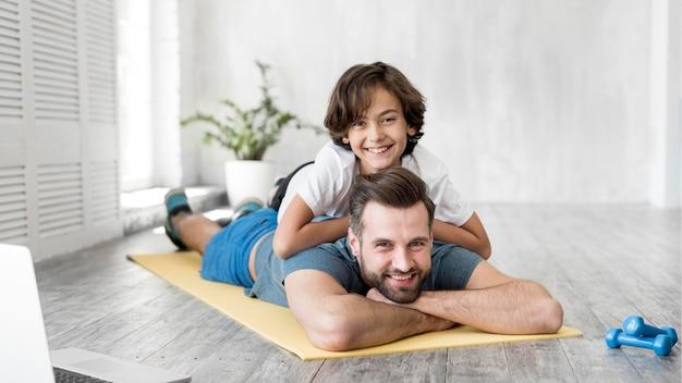 子供と彼の父親は家でスポーツをしています 無料写真