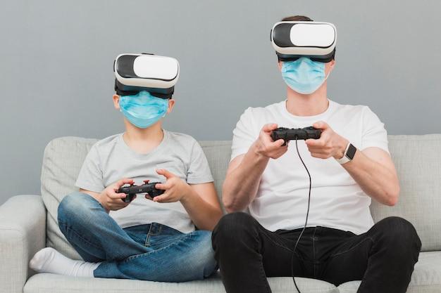 Вид спереди мальчика и человека, играя с гарнитурой виртуальной реальности во время ношения медицинских масок Бесплатные Фотографии