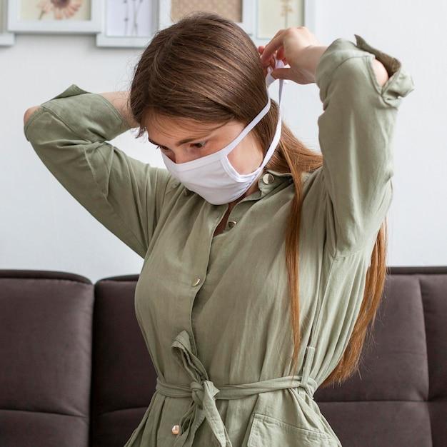 Женщина надевает медицинскую маску Бесплатные Фотографии