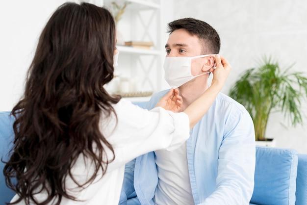 フェイスマスクをつける男を助ける女性の側面図 無料写真