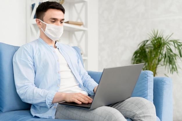 ノートパソコンで作業する医療マスクと自宅の男の側面図 無料写真