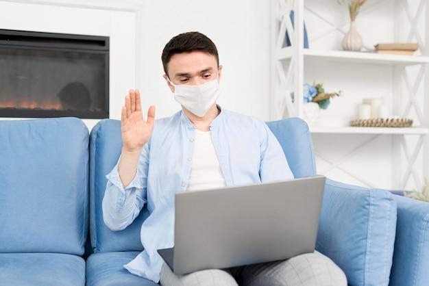 ラップトップに取り組んで医療マスクと自宅の男の正面図 無料写真