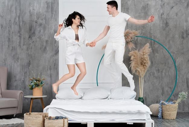 Счастливая пара прыгает в постели у себя дома Бесплатные Фотографии