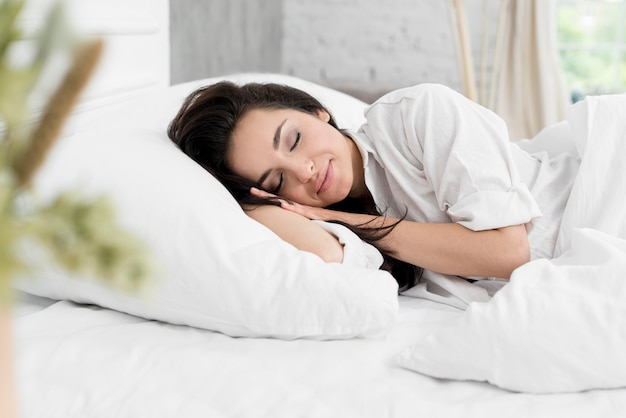 Вид сбоку женщина спит в постели Бесплатные Фотографии