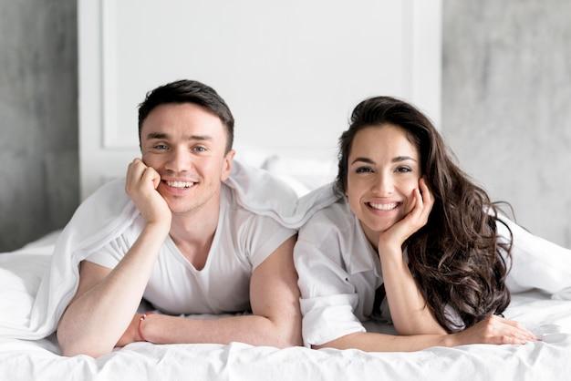 Вид спереди пара позирует в постели Бесплатные Фотографии