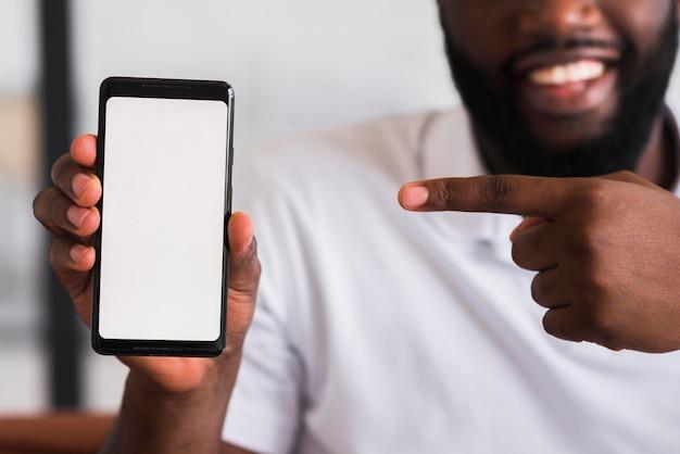 彼の携帯電話を提示するひげを生やした男 無料写真
