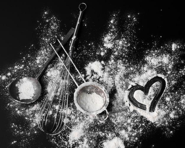 テーブルの上の砂糖粉末と泡立て器のトップビュー 無料写真