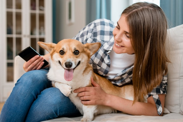 Вид спереди женщины, держащей смартфон и собака Бесплатные Фотографии