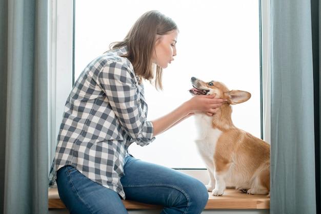 Вид сбоку женщины с ее собакой перед окном Бесплатные Фотографии