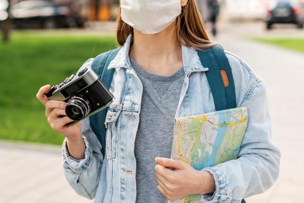 Путешественник в медицинской маске с картой и камерой Бесплатные Фотографии