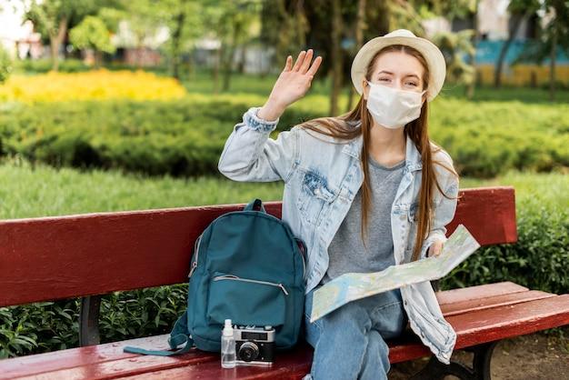 手を振っている医療マスクを身に着けている旅行者 無料写真