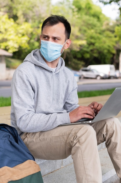屋外のラップトップに取り組んで医療マスクを持つ男の側面図 無料写真