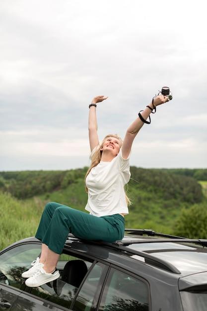 Женщина наслаждается жизнью во время позирует на вершине автомобиля Бесплатные Фотографии