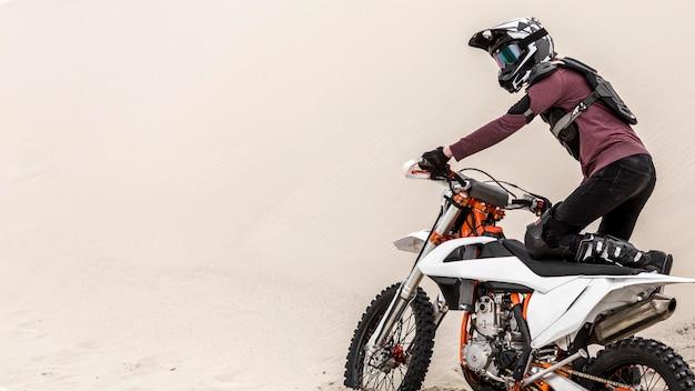 砂漠でバイクに乗るアクティブな男 無料写真