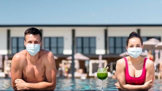 社会的距離を保つマスクを持つ男女 無料写真