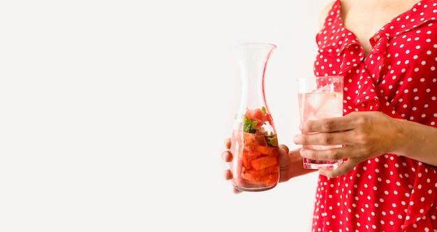 水とスイカのコピースペースとガラスを保持している女性 無料写真